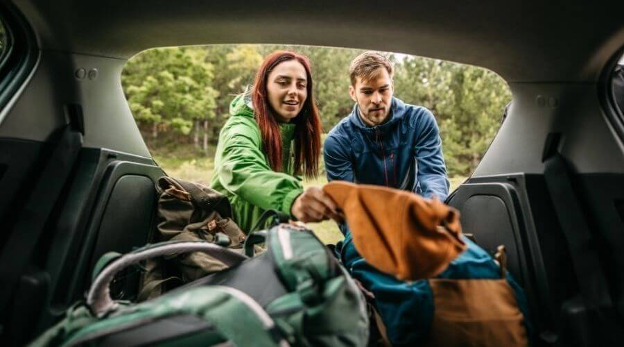 A couple packing for a winter car camping trip