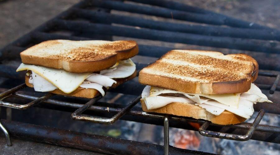 Two slices of toast laying on a stainless steel fire pit