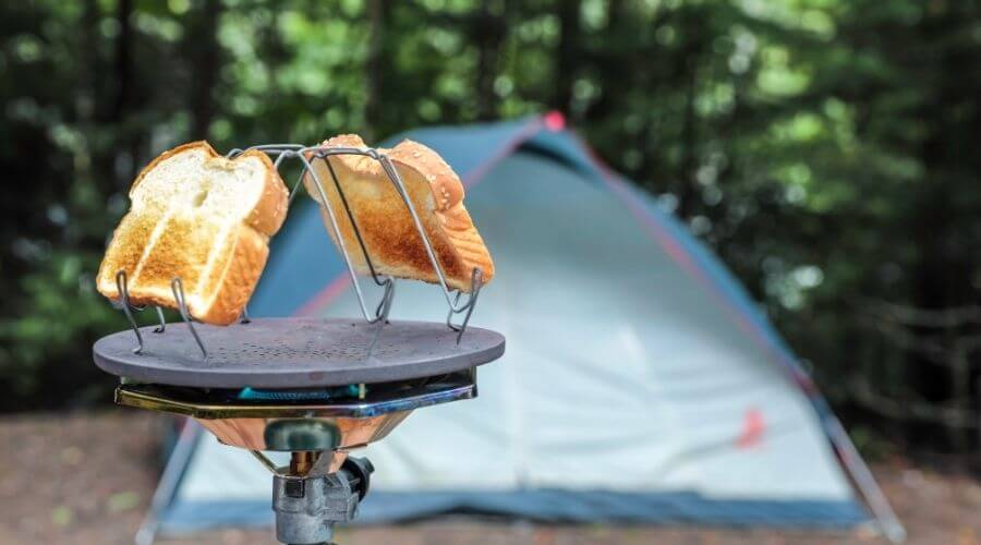 Folding camp stove toaster with a tent in the background