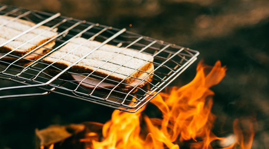 A portable BBQ grill basket with two toast inside held over a campfire