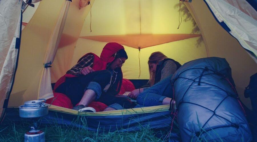 A couple playing games inside the tent in stormy weather