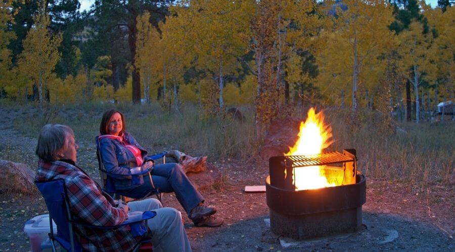 Two people sitting close to a campfire