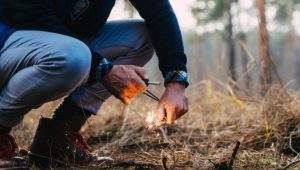 Man using camping lighter to start a fire in the woods